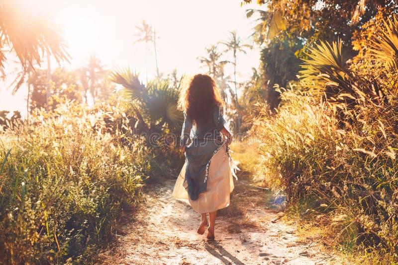 一个领域的美丽的少妇在日落 免版税库存图片