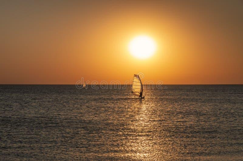 一个风帆冲浪者的剪影一个委员会的在风帆下沿镇静水表面移动在海的日落,天际 库存图片