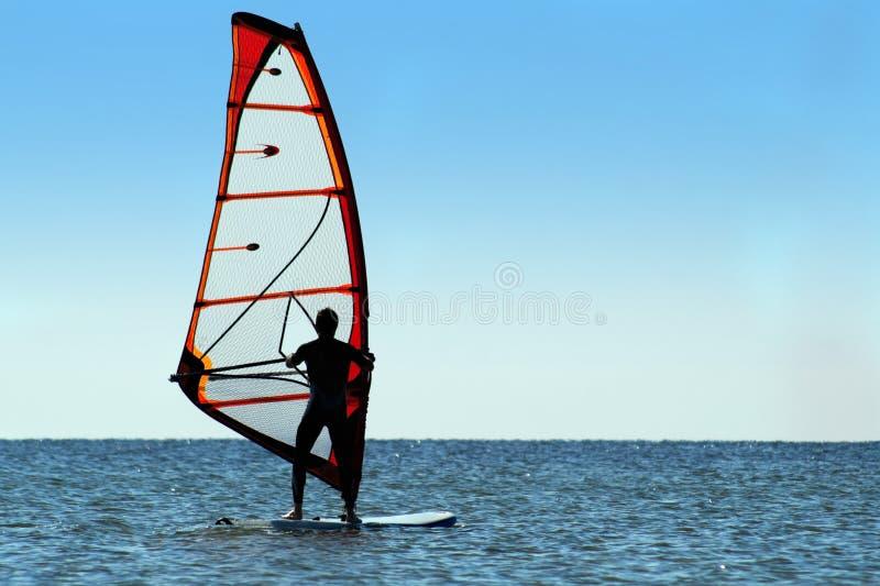 一个风帆冲浪者的剪影在海的 免版税库存图片