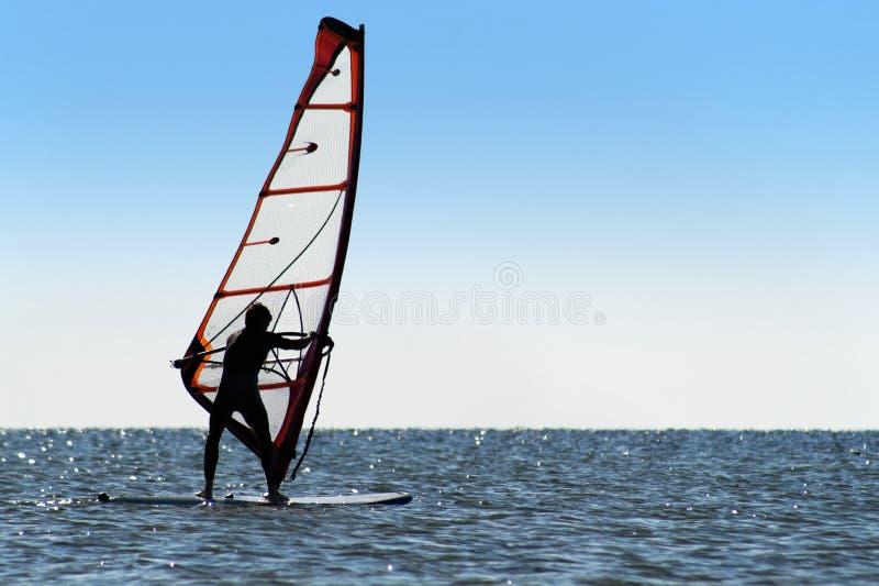 一个风帆冲浪者的剪影在蓝色海的 库存照片