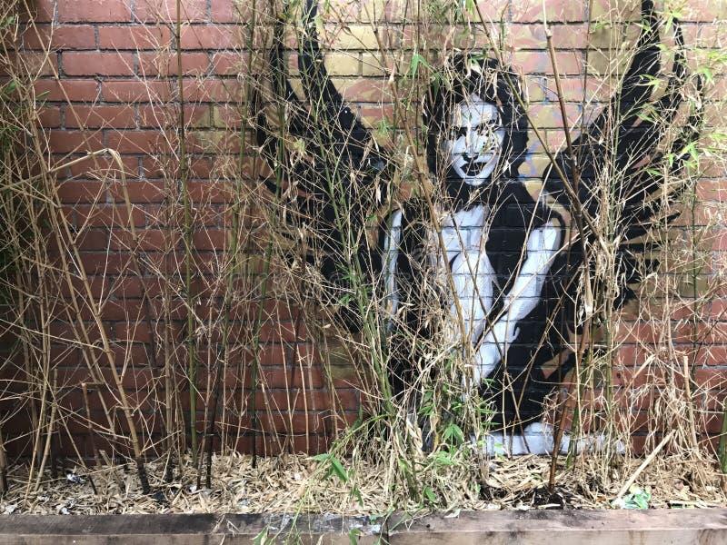 一个飞过的天使的街道画在叶子后的 库存照片