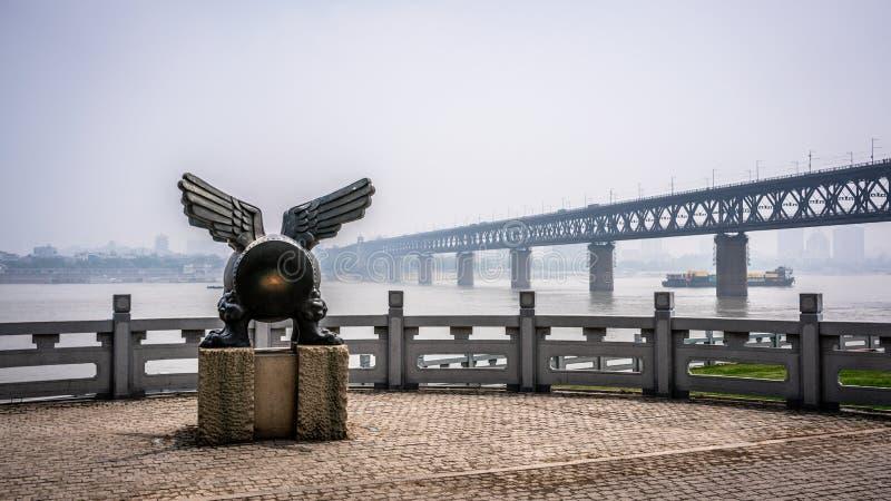 一个飞过的鼓的扬子武汉伟大的桥梁和雕象的风景看法在河岸的在武汉湖北中国 图库摄影