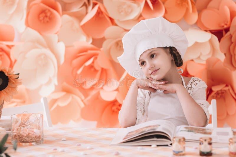 一个首要帽子的迷人的女孩站立在准备好的饭桌上烹调晚餐 库存照片