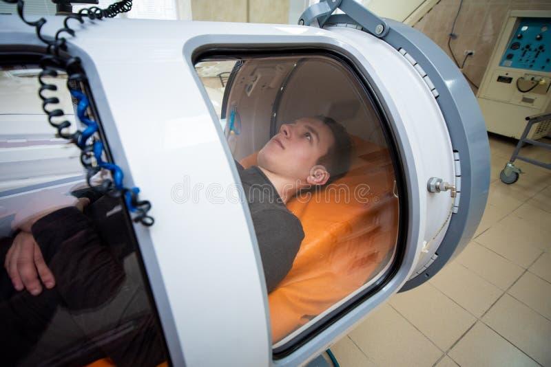 一个高压舱的年轻人,氧气治疗 免版税库存照片