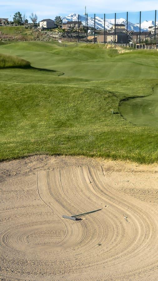 一个高尔夫球场的垂直的框架地堡和航路有家山和天空背景的 库存图片
