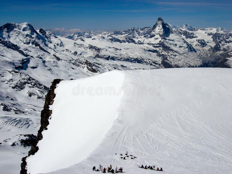 一个高山顶高原的许多偏远地区滑雪者在策马特附近的瑞士阿尔卑斯有马塔角的一个巨大看法在他们后的 免版税库存图片