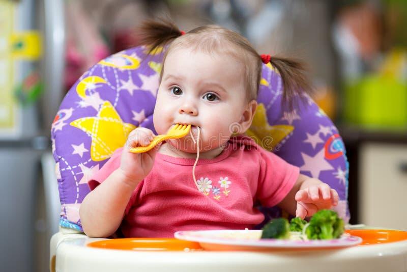 一个高脚椅子的小孩女孩哺养的与叉子 免版税库存图片