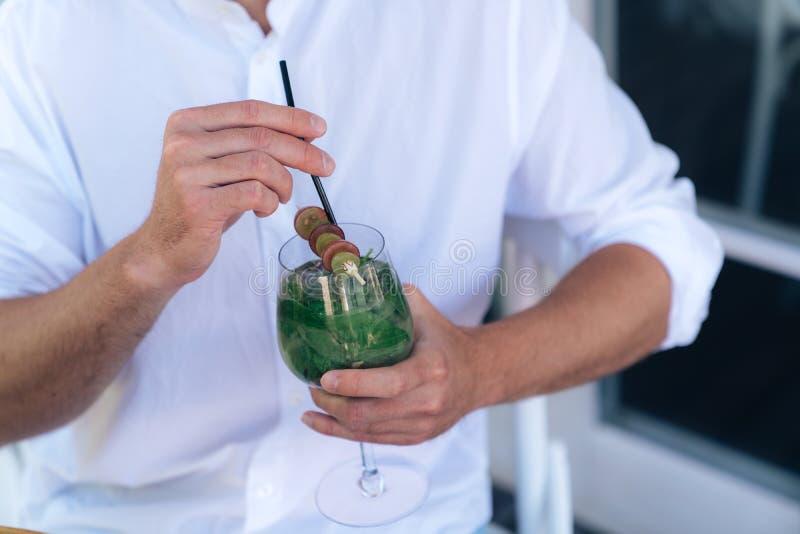 一个鸡尾酒的一个播种的框架的特写镜头用薄菏在男性手上 一件白色衬衣的一个人拿着与a的一块玻璃 免版税库存图片