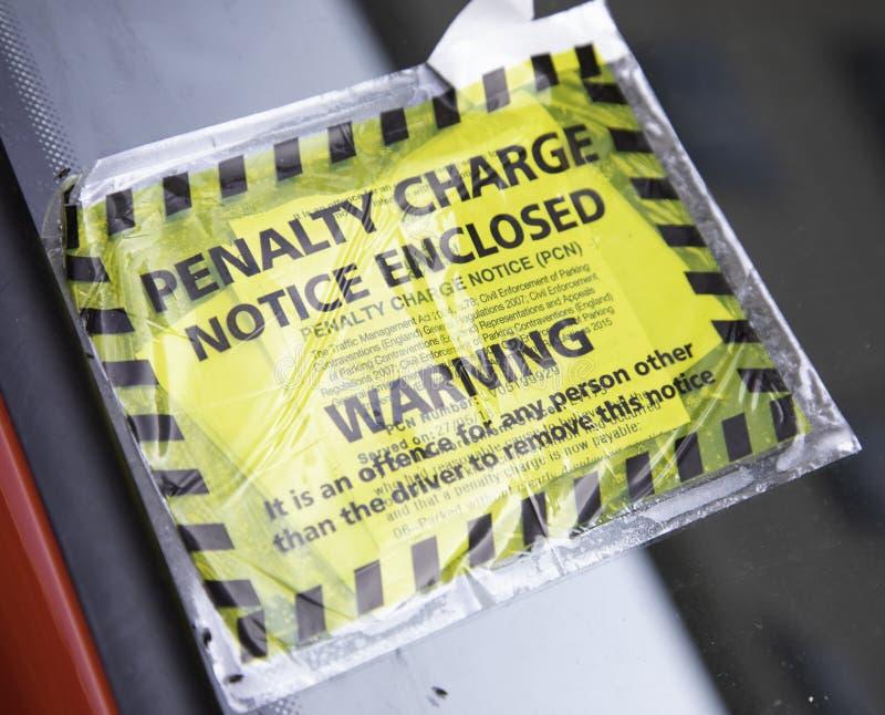 一个黄色和黑停车处penaty充电通知附有pa 免版税图库摄影