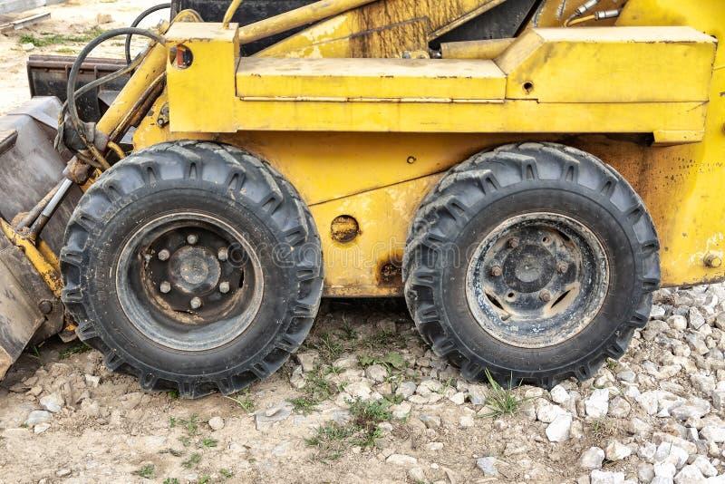 一个黄色微型挖掘机轮子的特写镜头在建造场所的 免版税库存照片