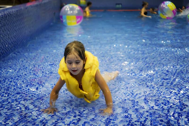 一个黄色救生衣游泳的一个小快乐的女孩在水池的水中在一个闭合的水公园 孩子学会游泳 免版税库存图片