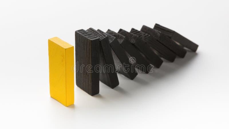 一个黄色木块停止下跌象多米诺的其他部分 库存照片