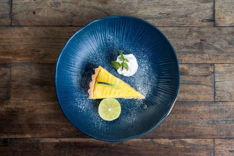 一个黄色柠檬酱蛋糕的顶视图图象在蓝色陶瓷板材的 免版税库存图片