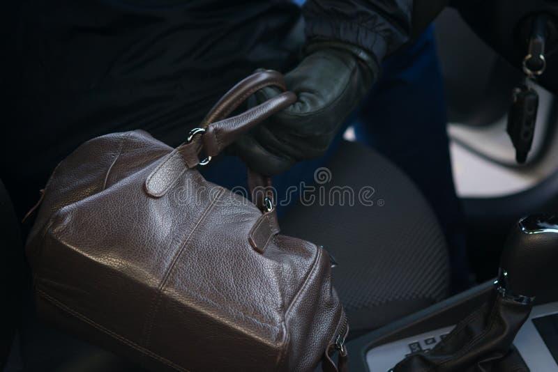 一个黑暗的敞篷的一个人通过车窗窃取从位子的妇女的提包,特写镜头 免版税图库摄影
