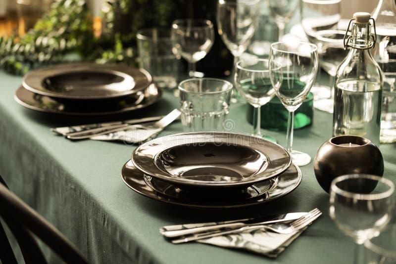 一个黑暗的用餐的集合的特写镜头在一张典雅的桌上的与在餐馆内部的绿色布料 r 库存照片