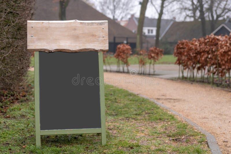 一个黑板标志的大模型与一些木头的在上面 图库摄影