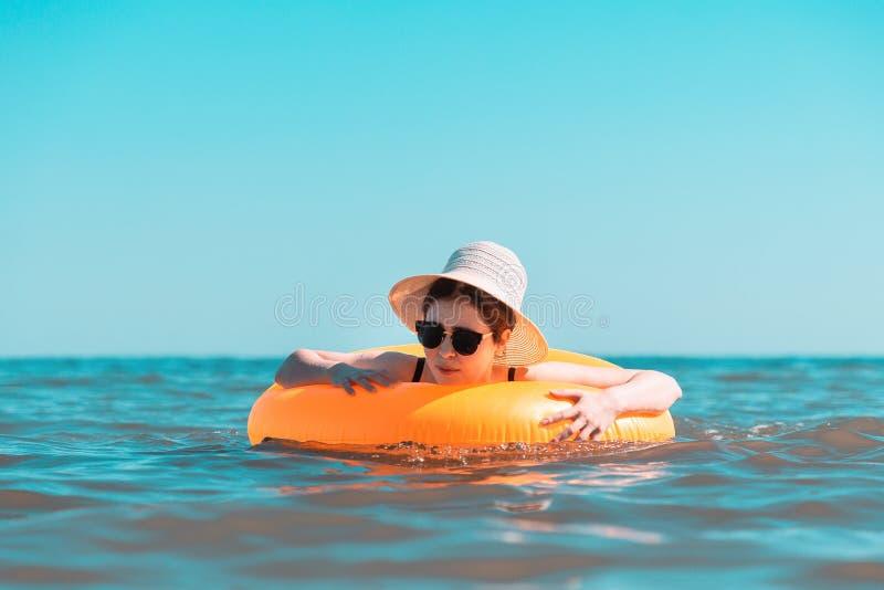 一个黑泳装和帽子的一年轻女人学会游泳与圈子 在恐惧和痛苦的情感的面孔 ??  库存图片
