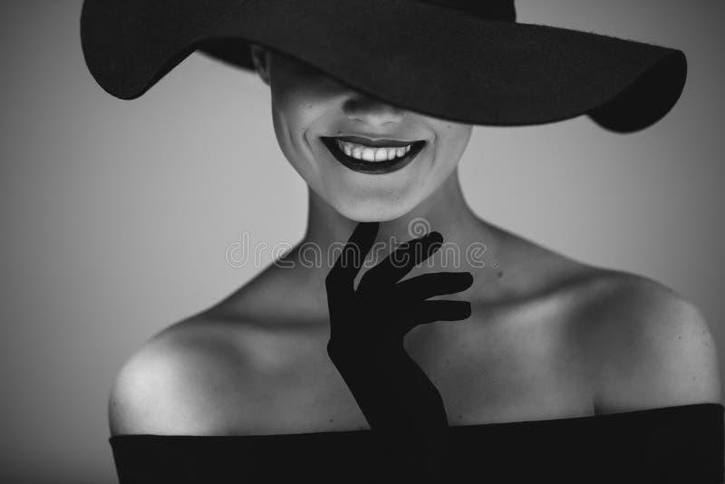 一个黑礼服和帽子的典雅的美丽的妇女 免版税库存图片