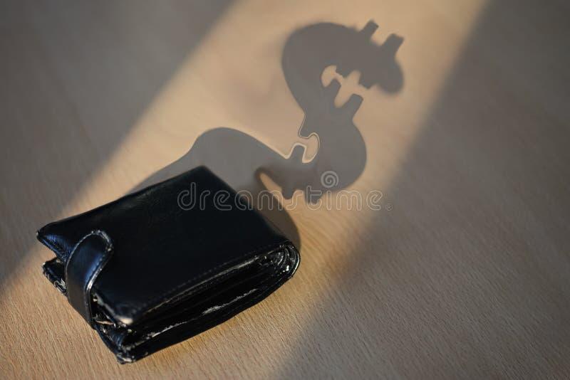 一个黑钱包美元形式的阴影在办公桌上的 库存照片