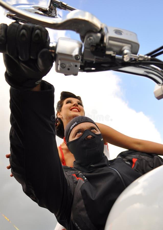 一个黑面具的一个人在一辆白色摩托车的轮子后在他后的坐美女坐天空蔚蓝的背景 库存图片