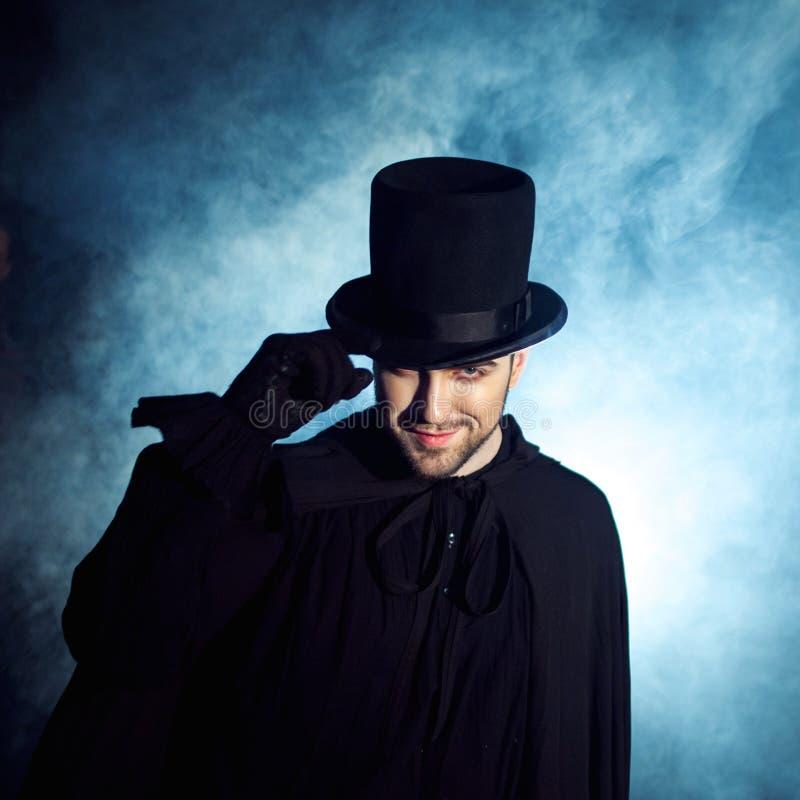 一个黑高顶丝质礼帽和斗篷的人 恶魔般的图象 魔术师魔术师 库存照片