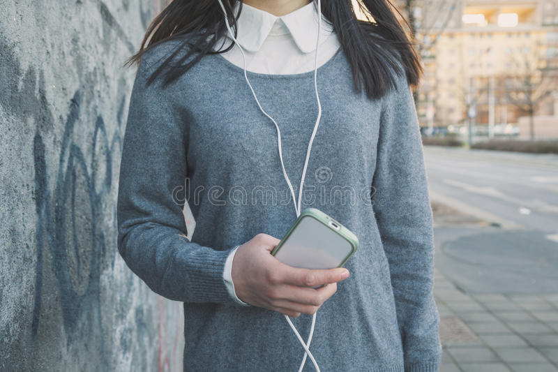 一个年轻中国女孩的细节有电话的 免版税图库摄影