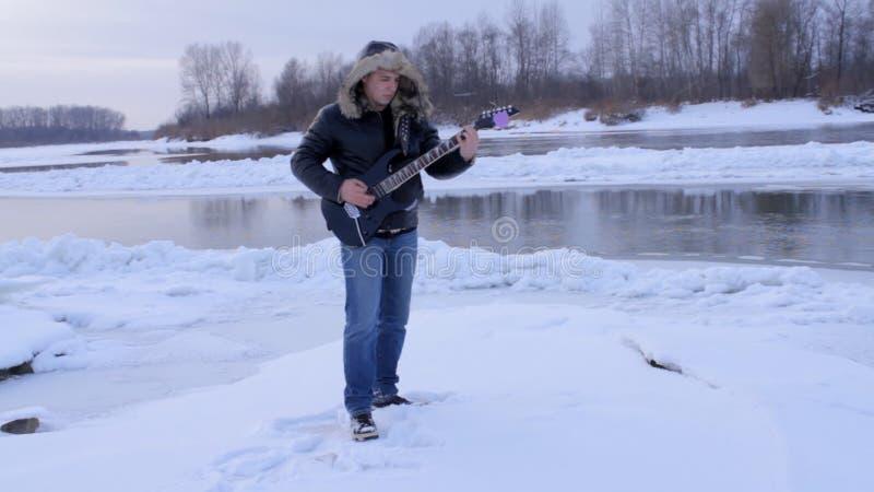 一个年轻人在弹吉他的冬天 股票视频