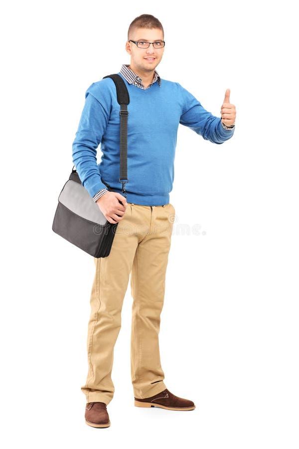 一个年轻人的全长画象有给a的有肩带的女用手提包的 免版税库存照片