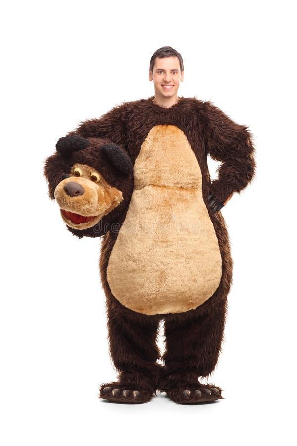 一个年轻人的全长画象熊服装的 库存照片