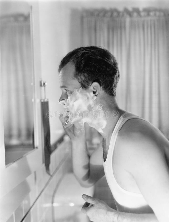 一个年轻人的档案在一个镜子前面的在卫生间刮(所有人被描述不是更长的生存和没有庄园exis 免版税库存照片
