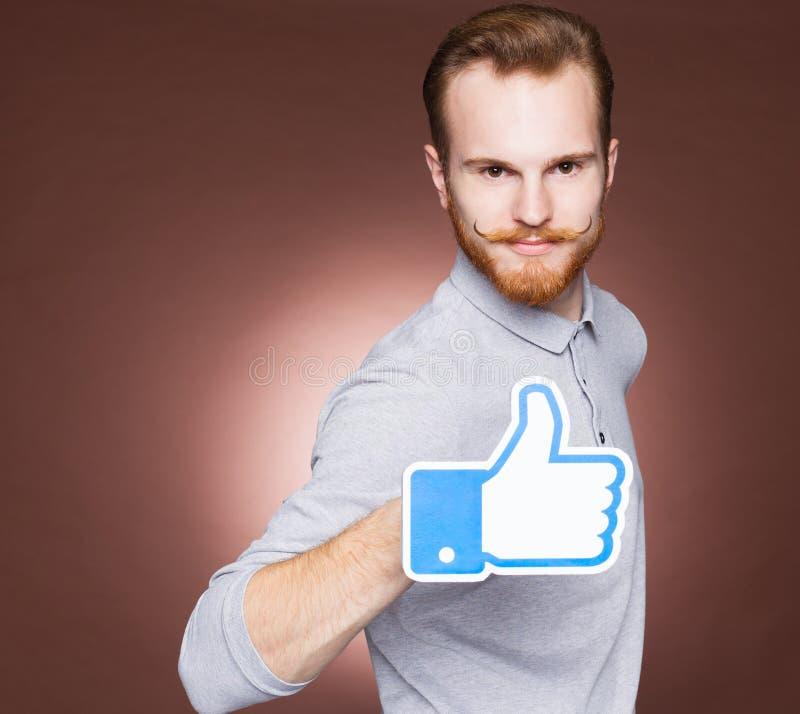 一个年轻人的画象有髭和胡子牛仔裤和格子花呢上衣行家的样式在演播室 显示一个标志象 关闭 免版税库存照片