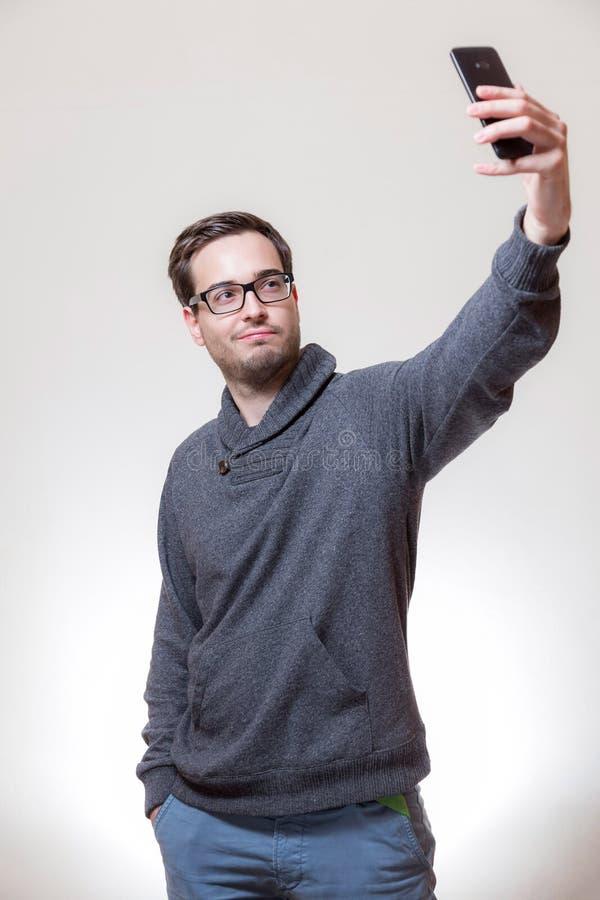 一个年轻人采取与他的手机的一张自画象 免版税库存图片