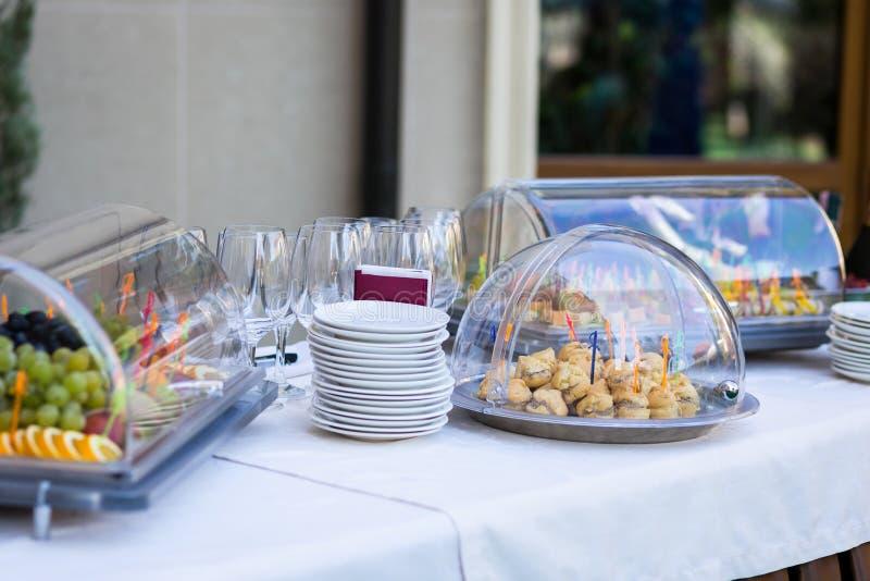 一个宴会的宴会桌在餐馆 快餐,蛋糕,空的玻璃,碗筷,板材,在板材的果子 库存照片