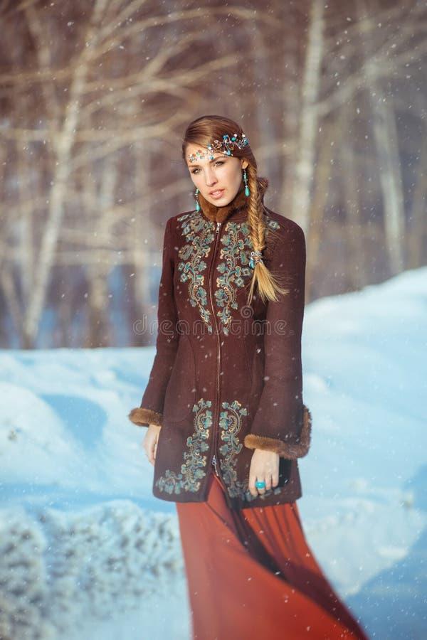 一个年轻俏丽的女孩在森林里走在冬天 库存图片