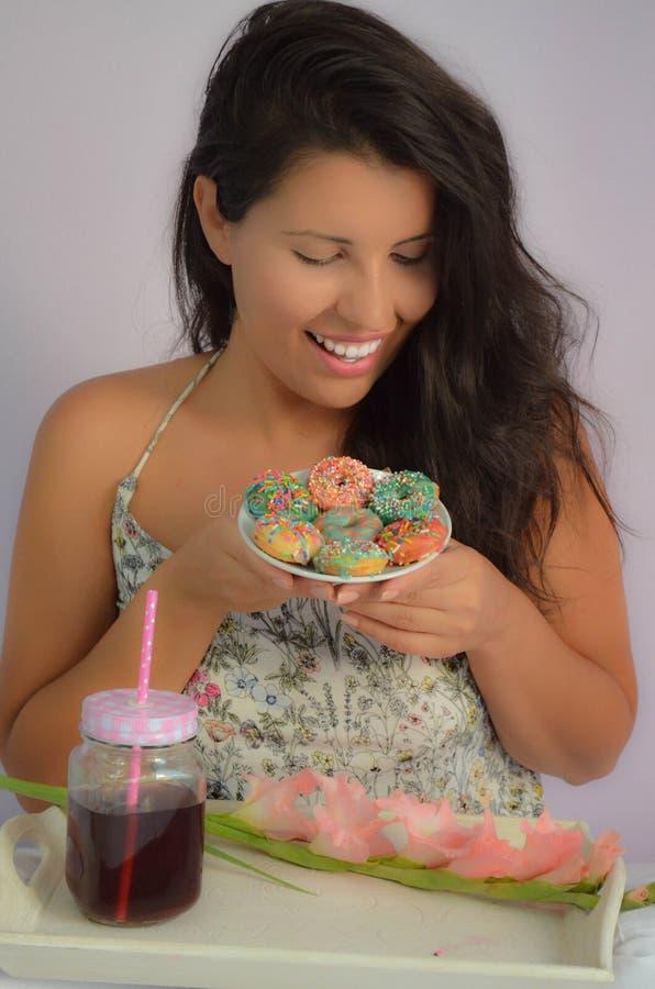 一个黑发模型在美国油炸圈饼享用早餐 库存图片