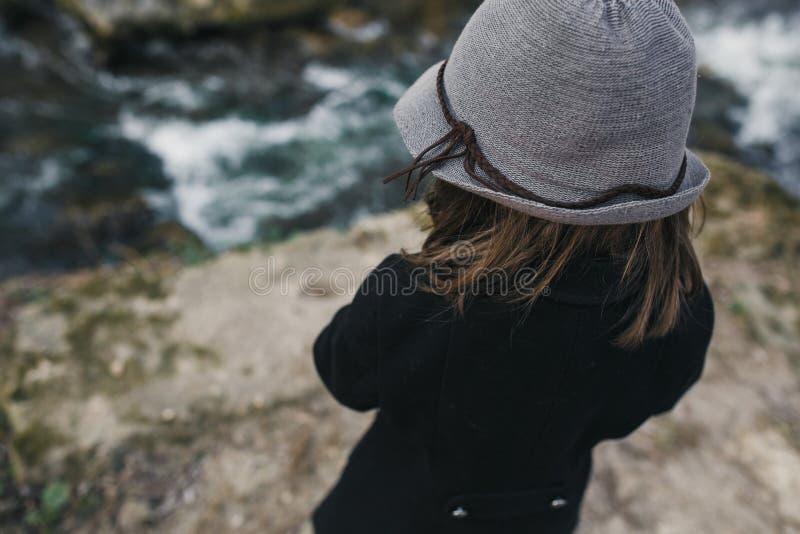 一个黑外套和帽子的小女孩 免版税库存图片