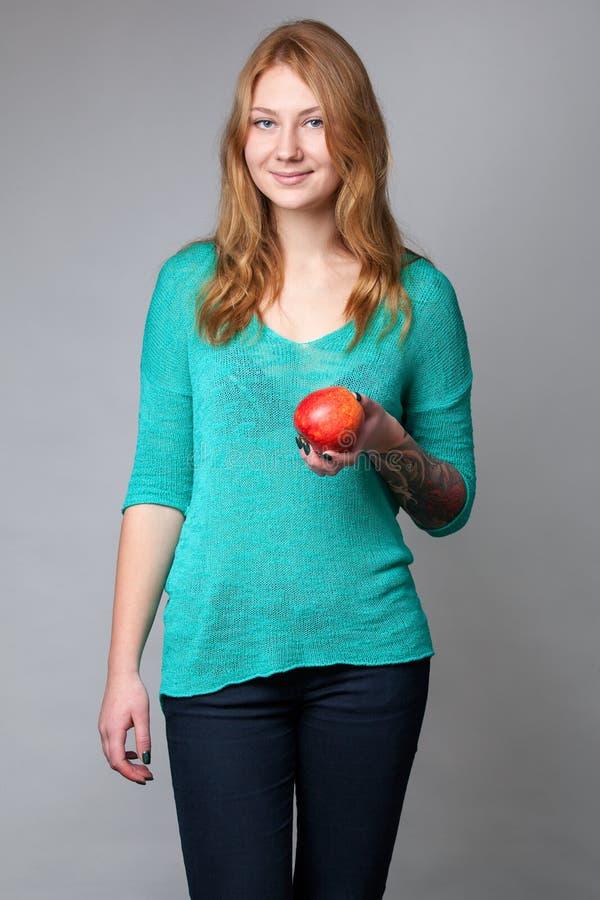 一个年轻姜夫人的画象绿松石女衬衫的有appl的 免版税库存图片