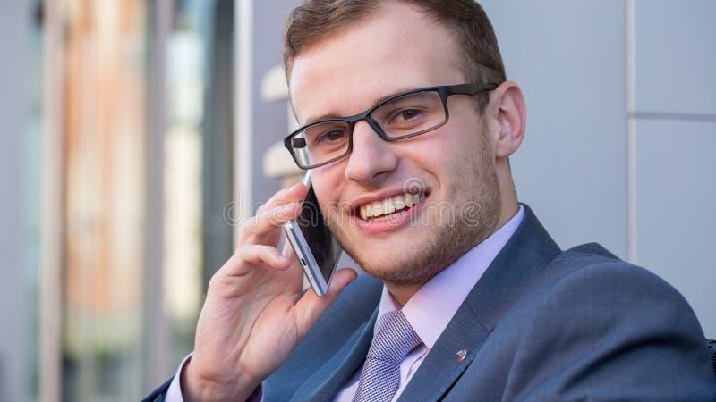 一个25岁的有领带和手机的商人和衬衣的首肩射击衣服的。 免版税库存图片