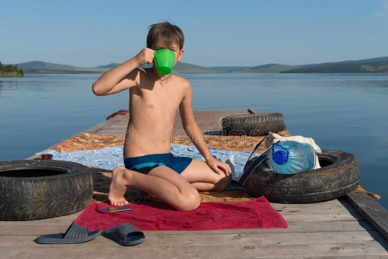 一个11岁的男孩在一个晴朗的夏日时喝从杯子的水,当坐一个木码头反对岸和湖 库存图片