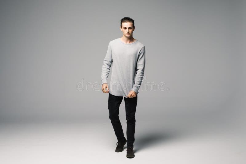 一个年轻时尚人的全长照片用他的手折叠了,调查照相机和微笑 在灰色背景 库存照片