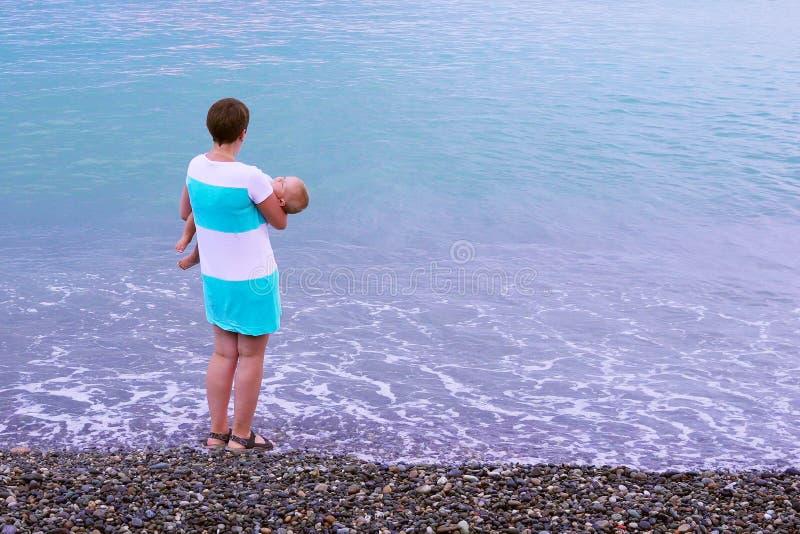 一个年轻母亲是在与她睡觉的婴孩的海滩 库存照片