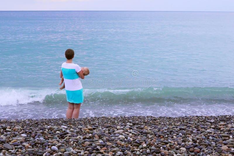 一个年轻母亲是在与她睡觉的婴孩的海滩 免版税库存图片
