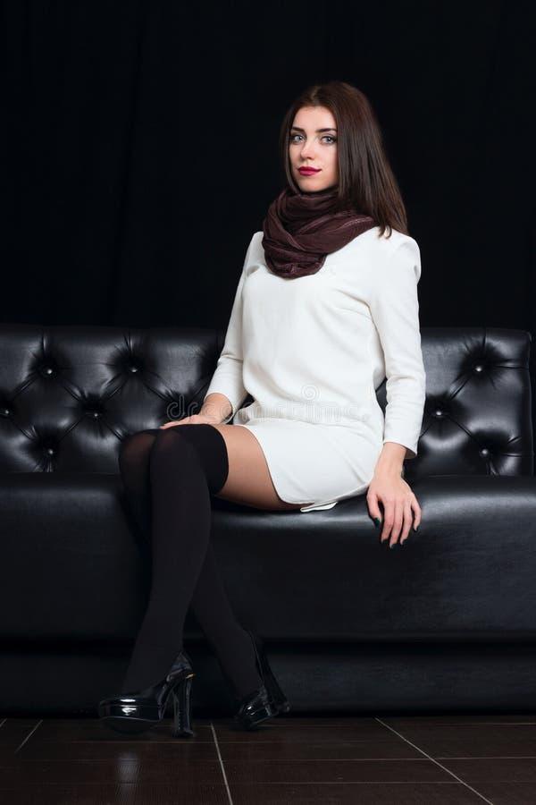 一个黑沙发的俏丽的妇女 库存图片