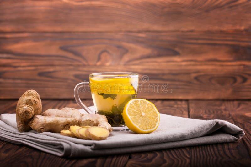 一个玻璃杯子有很多绿茶 在木背景的一个杯子 在姜和柠檬旁边的一个小杯子在桌布 复制空间 库存图片