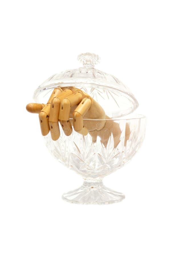 从一个玻璃箱子confectionerys出来的被明确表达的木手 图库摄影
