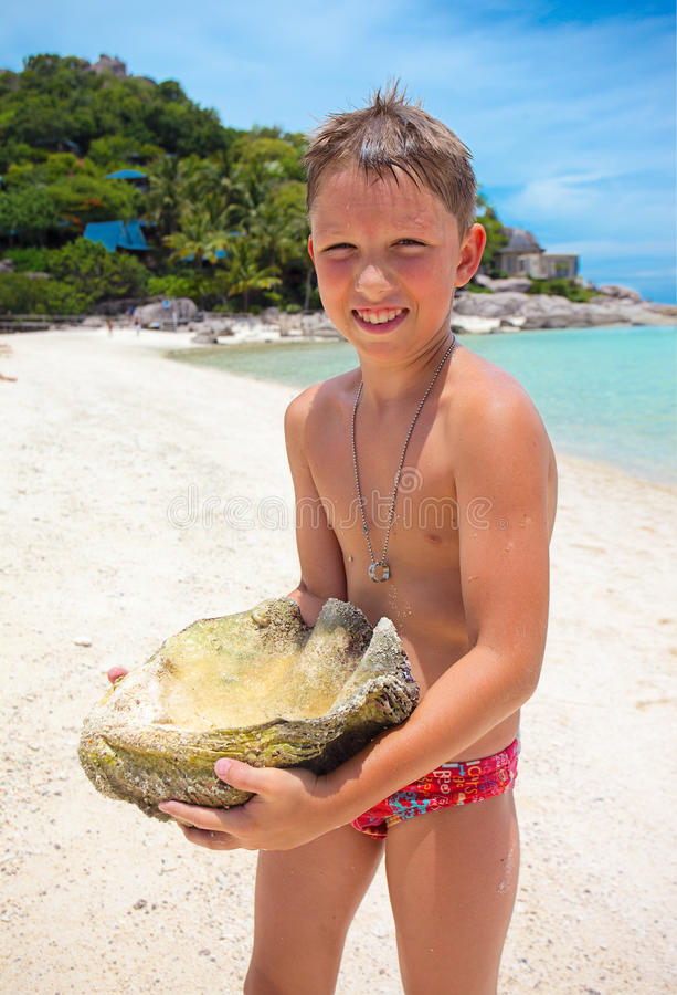 一个年轻男孩举行的大贝壳 免版税库存照片