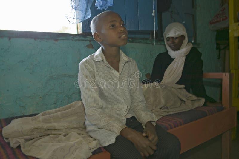 一个年轻男孩在感染在Pepo La Tumaini Jangwani的HIV/AIDS他的母亲坐, HIV/AIDS公共Rehabi的床边  库存图片