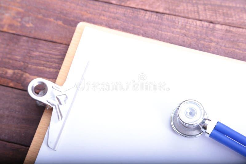一个医疗听诊器的特写镜头有文件夹的在木背景 免版税库存图片