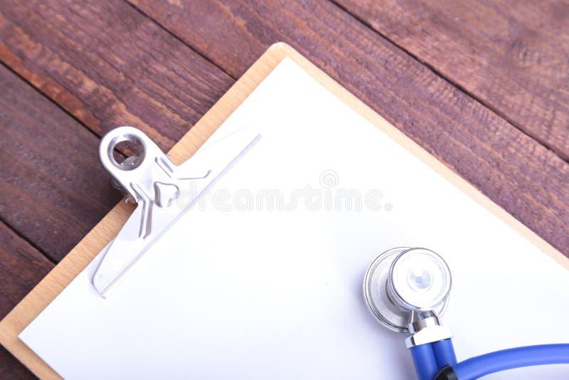 一个医疗听诊器的特写镜头有文件夹的在木背景 库存图片