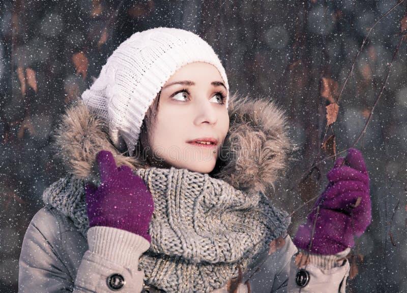 一个年轻白肤金发的女孩的画象在冬天森林里在公园 图库摄影